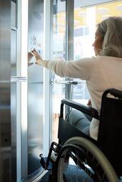 Das Bild zeigt eine Frau im Rollstuhl, die den Aufzug benutzt.