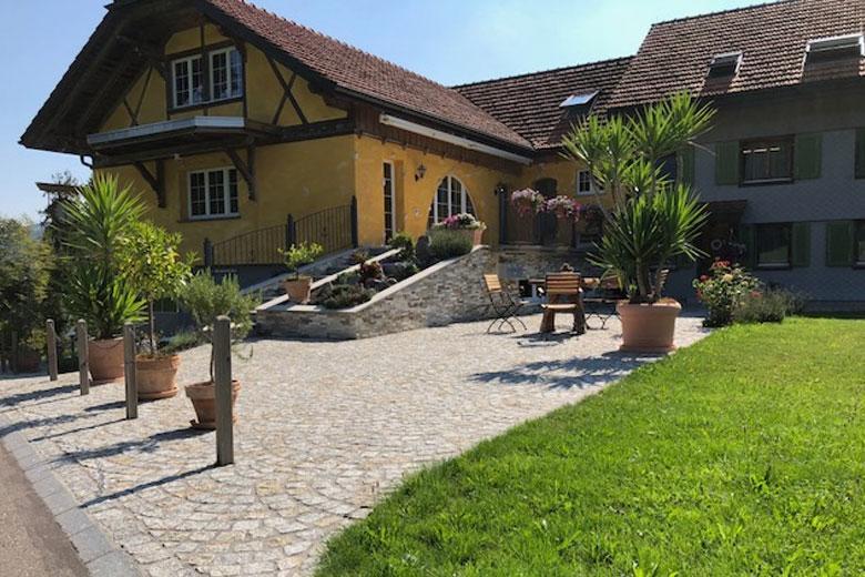 SAKRET Schweiz Referenzen | Natursteinboden vor Haus Frontalansicht