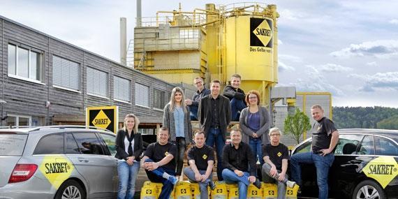 SAKRET Schweiz Mitarbeiter vor Dienstwägen und Silo