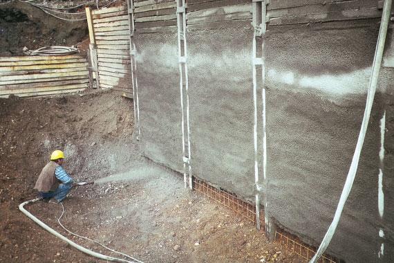 Baugrubensicherung | Bauarbeiter setzt Wand instand mit Maschine