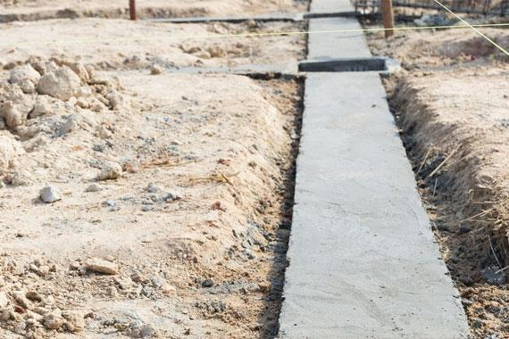 Streifenfundament selbst erstellen für Gartenmauer, Gabionen und Gartenhaus | gesetztes Streifenfundament in sandiger Umgebung