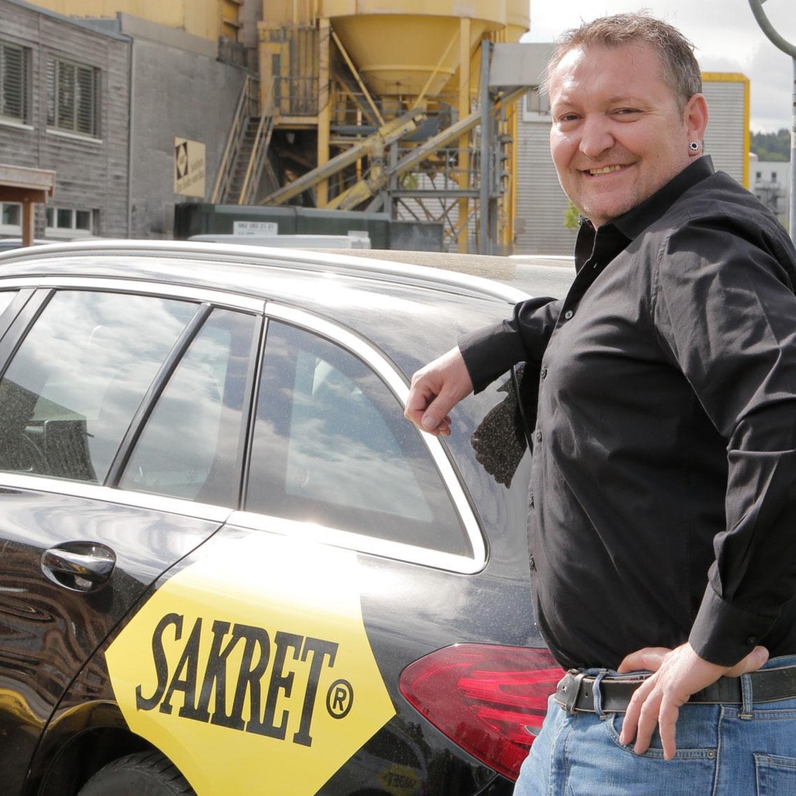 SAKRET Fahrzeugflotte Branding | Mitarbeiter vor SAKRET-Auto