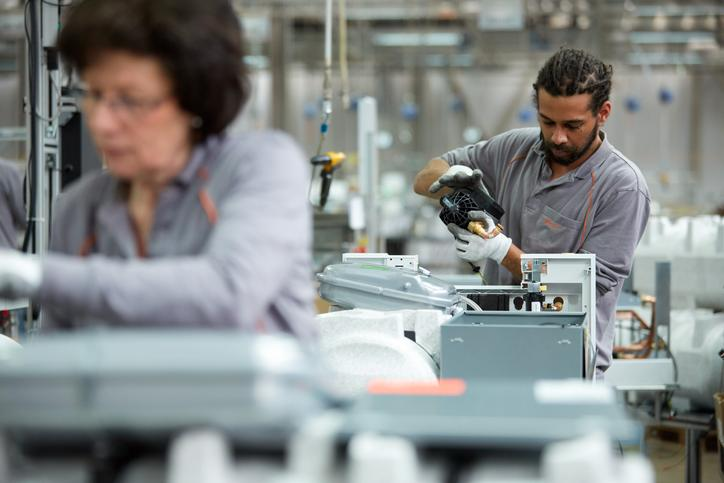 The image shows a woman and a man working in the Allendorf Viessmann factory.