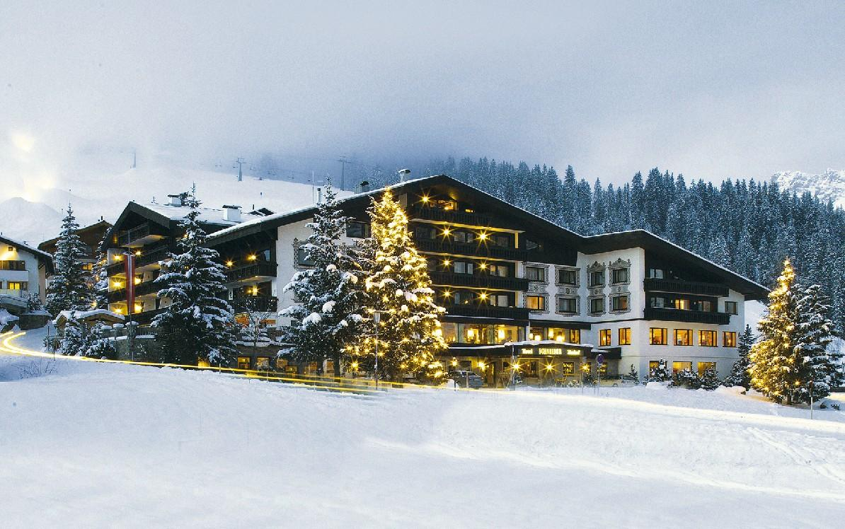 Das Bild zeigt das Hotel Almhof Schneider in Lech in einer Winterlandschaft.
