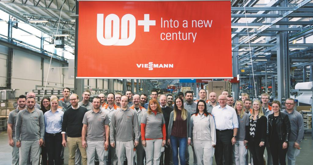 Viessmann employees stand under the 100 years+ banner