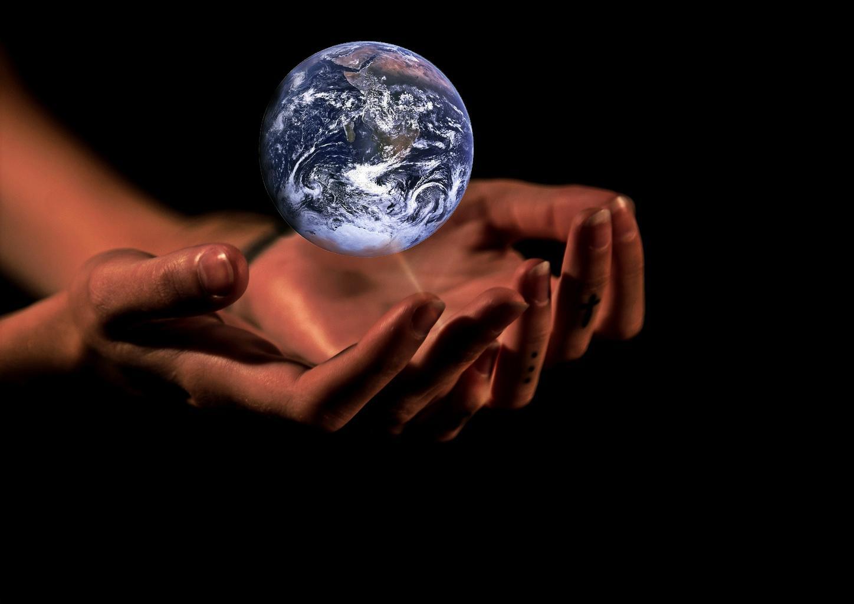 Das Bild zeigt die Erde als leuchtende Kugel über menschliche Hände.