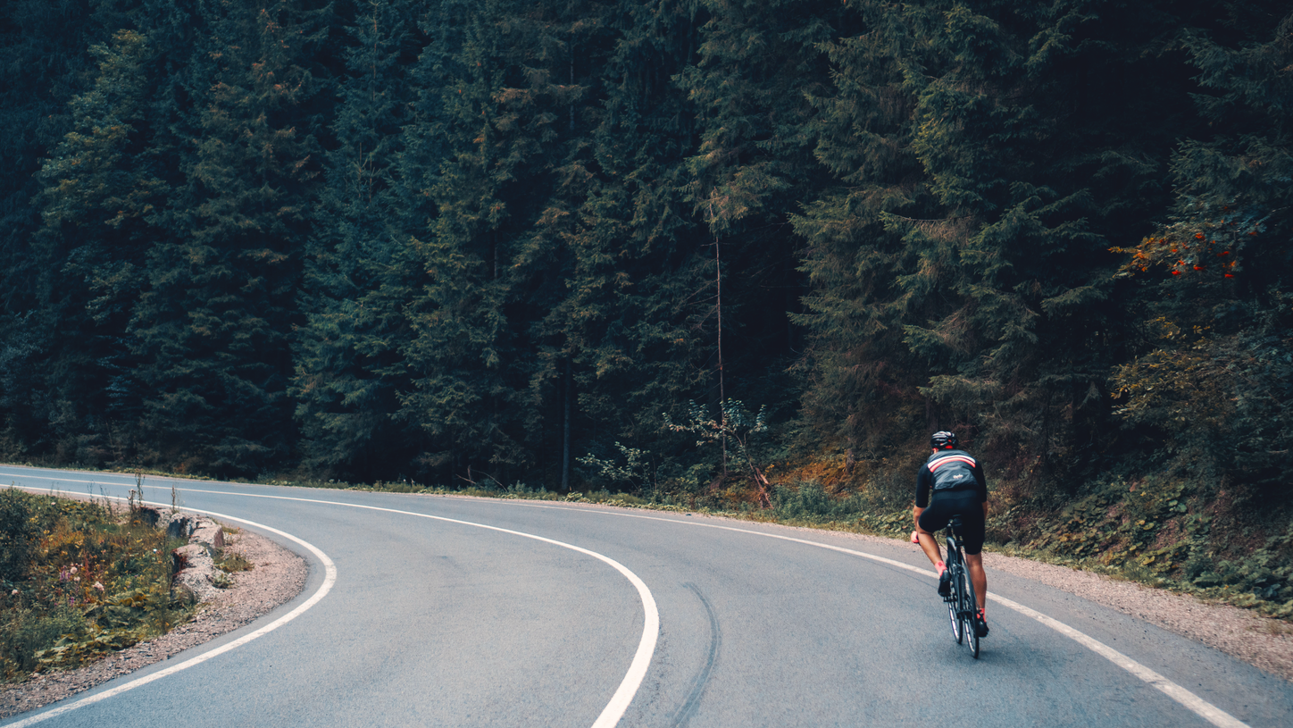The picture shows a cyclist on a mountain road