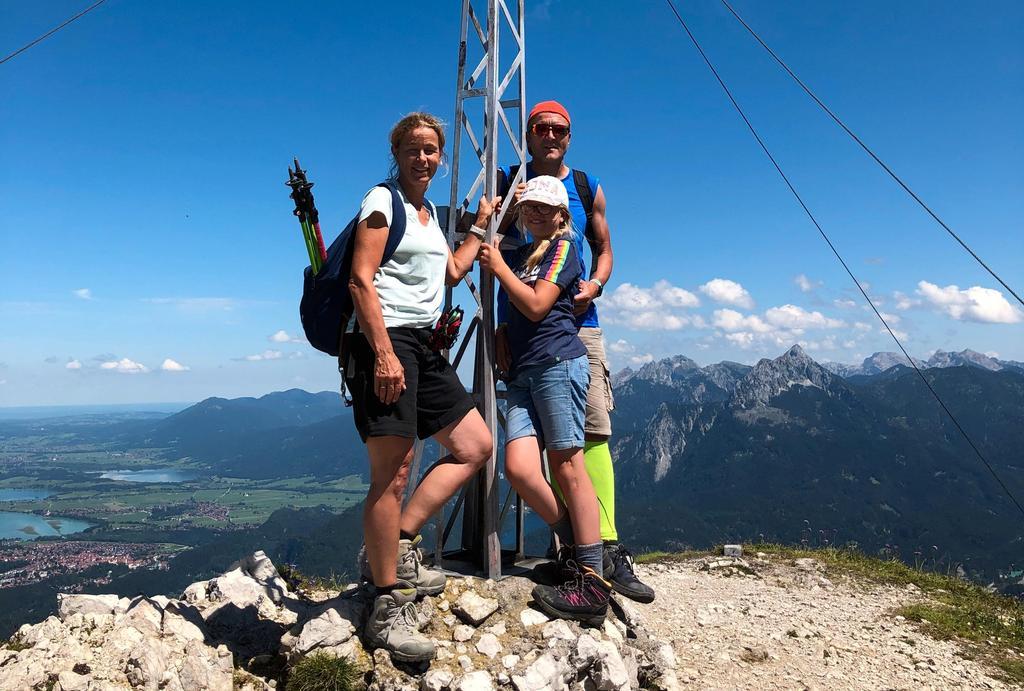 Das Bild zeigt eine sportliche Familie am Gipfelkreuz