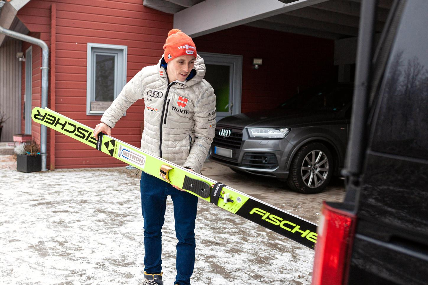 The image shows Eric Frenzel with his skis in front of his house.