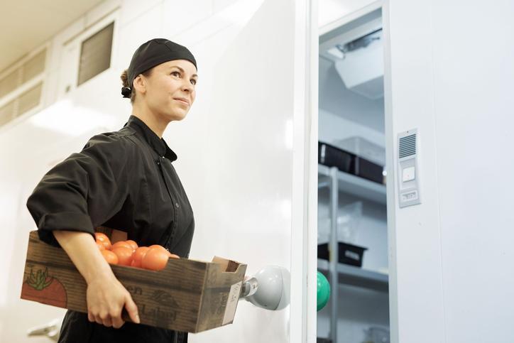 Das Bild zeigt eine Frau am Kühlhaus.