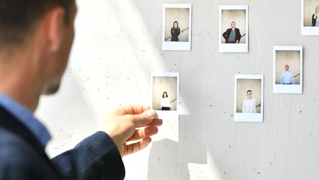 The picture shows a man in front of a wall with portraits