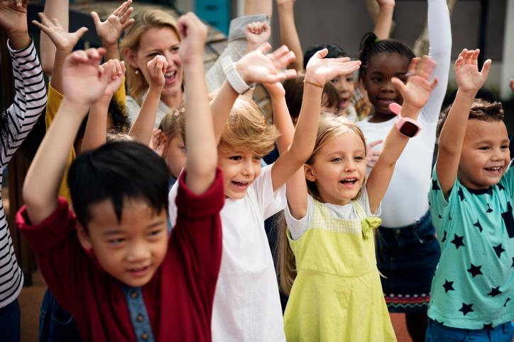 Image shows laughing children with arms up.