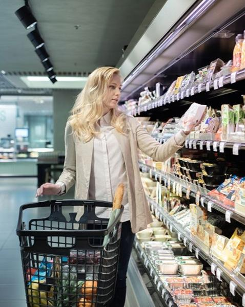 The image shows a woman at the refrigerated shelf.