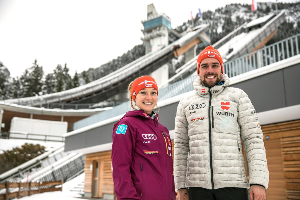 The image shows ski jumper Katharina Althaus and Nordic combined athlete Johannes Rydzek in front of the ski jump in Oberstdorf