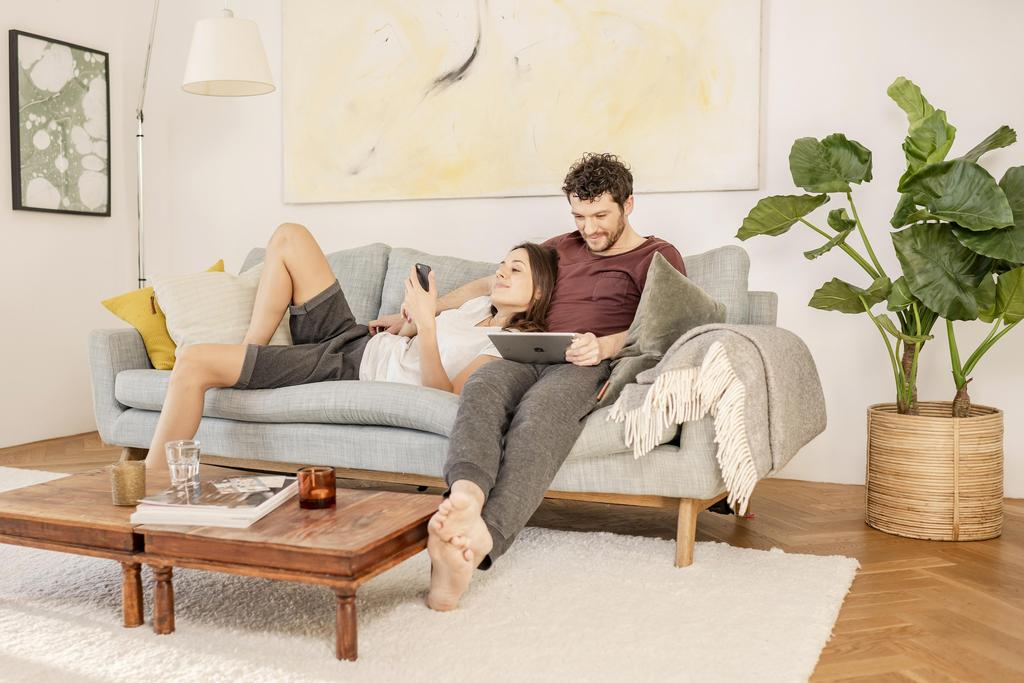 The picture shows a young couple on the sofa.