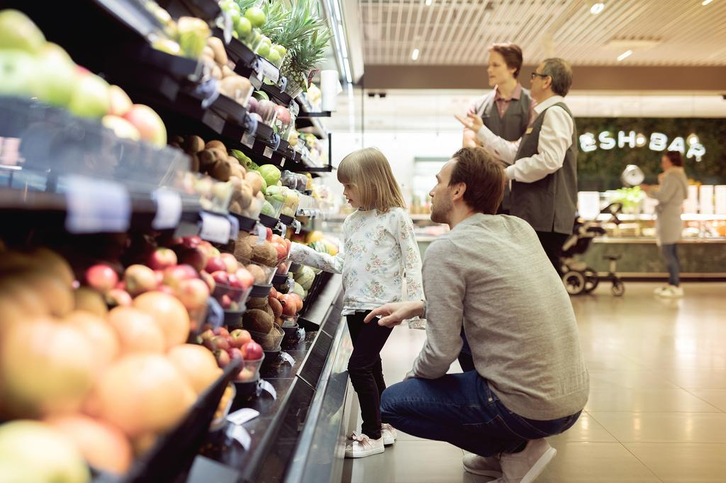 The image shows daughter and father shopping in the fruit department.