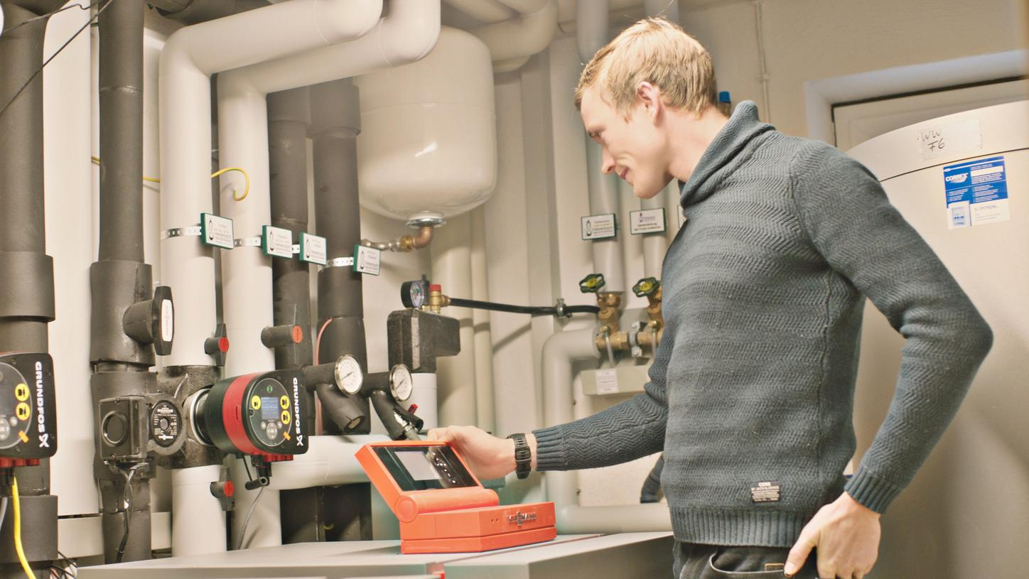 The image shows Benedikt Doll at the heating control.