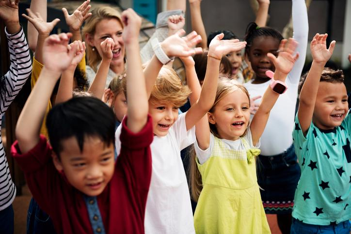 The image shows children with arms stretched towards the sky.