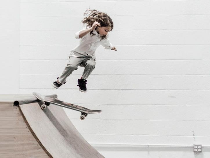 The picture shows a child skateboarding