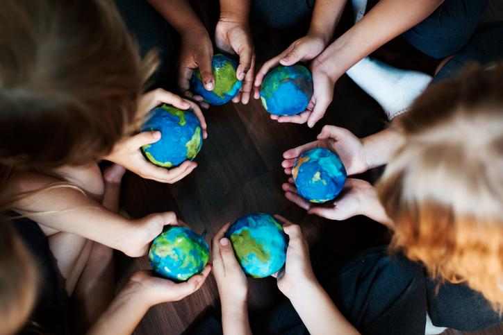 The image shows children's hands with globes made of plasticine.