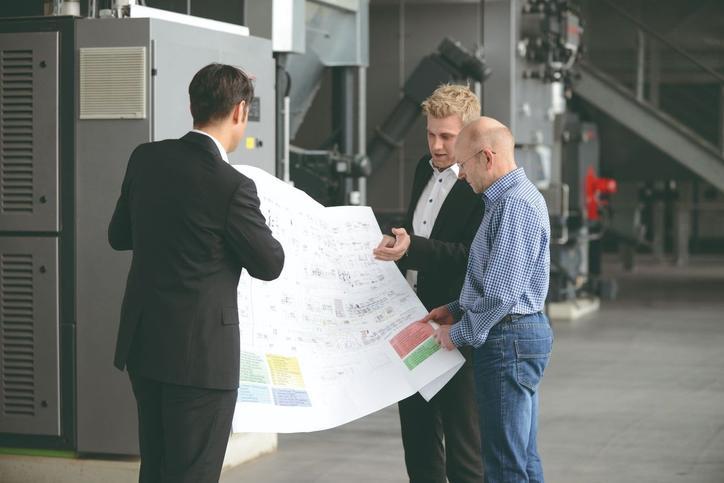 Das Bild zeigt drei Personen, die eine technische Zeichnung diskutieren