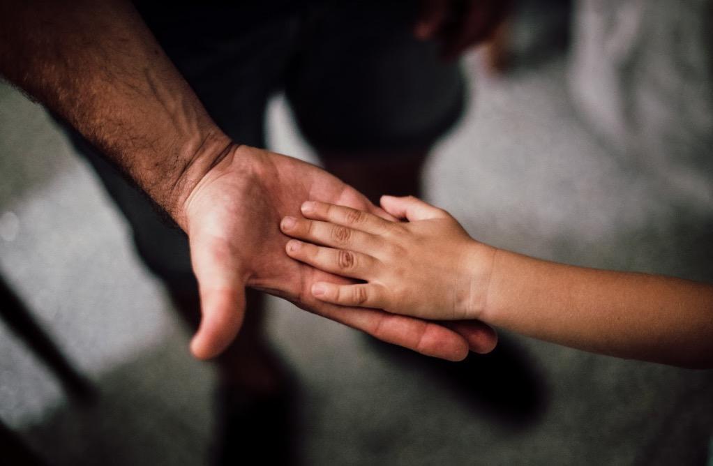 Das Bild zeigt zwei Hände, die sich berühren