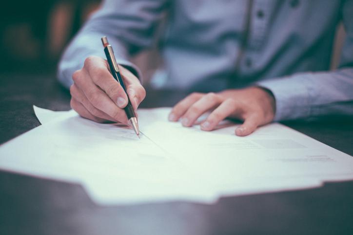 Das Bild zeigt eine Person, wie sie einen Vertrag unterschreibt.