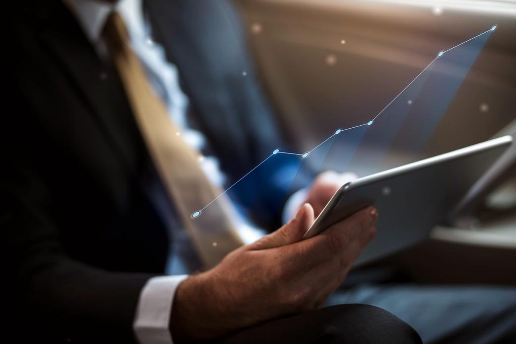 Image shows person with tablet as symbol for investments.