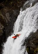 The image shows a person in a kayak on a waterfall.