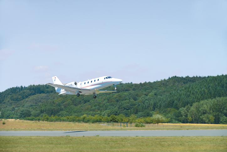 The image shows an airplane taking off from the airfield in Allendorf.