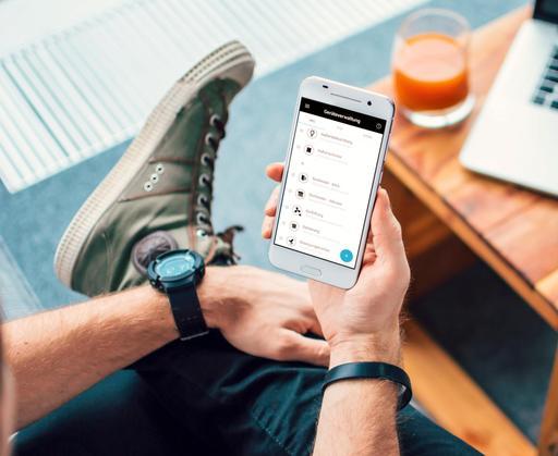 Ein Mann schaut sich die wibutler App auf dem Smartphone an