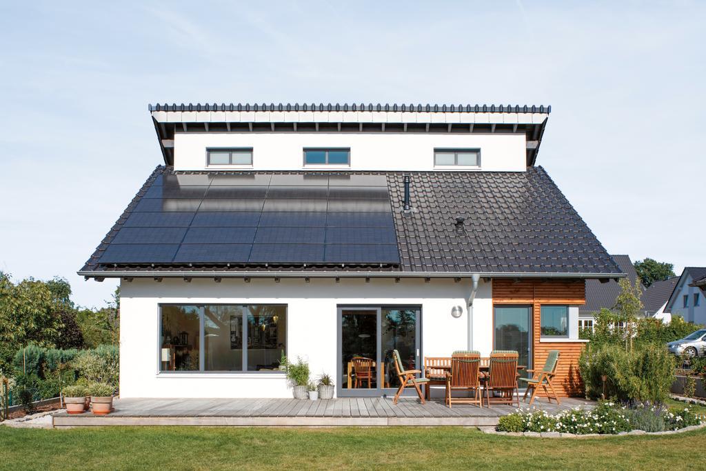 Das Bild zeigt ein modernes Einfamilienhaus mit Photovoltaik-Anlage.