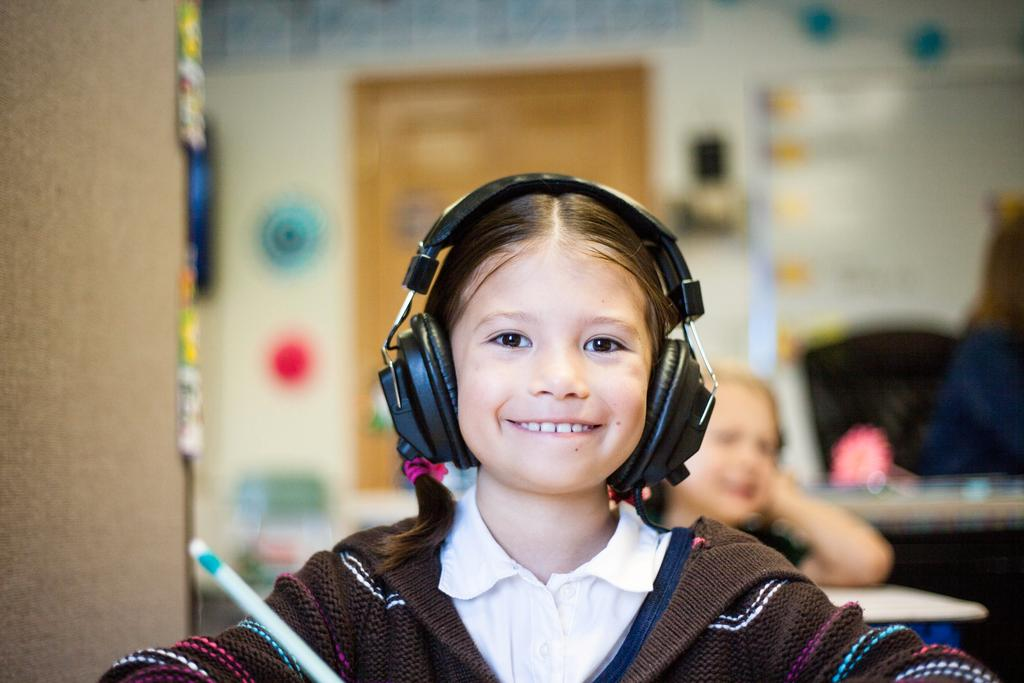 Junges Mädchen sitzt im Klassenraum und trägt Kopfhörer