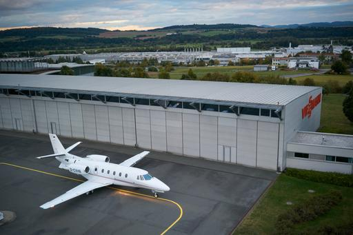The image shows an aircraft in front of the hangar.