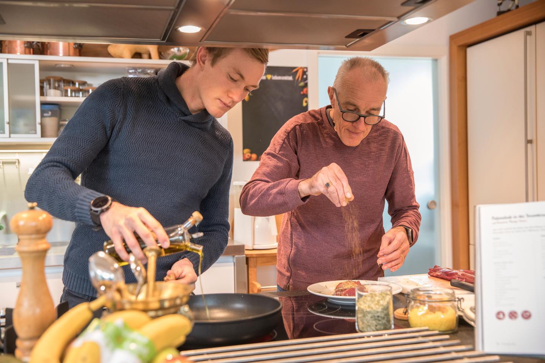 Das Bild zeigt Benedikt Doll mit Vater in der Küche.