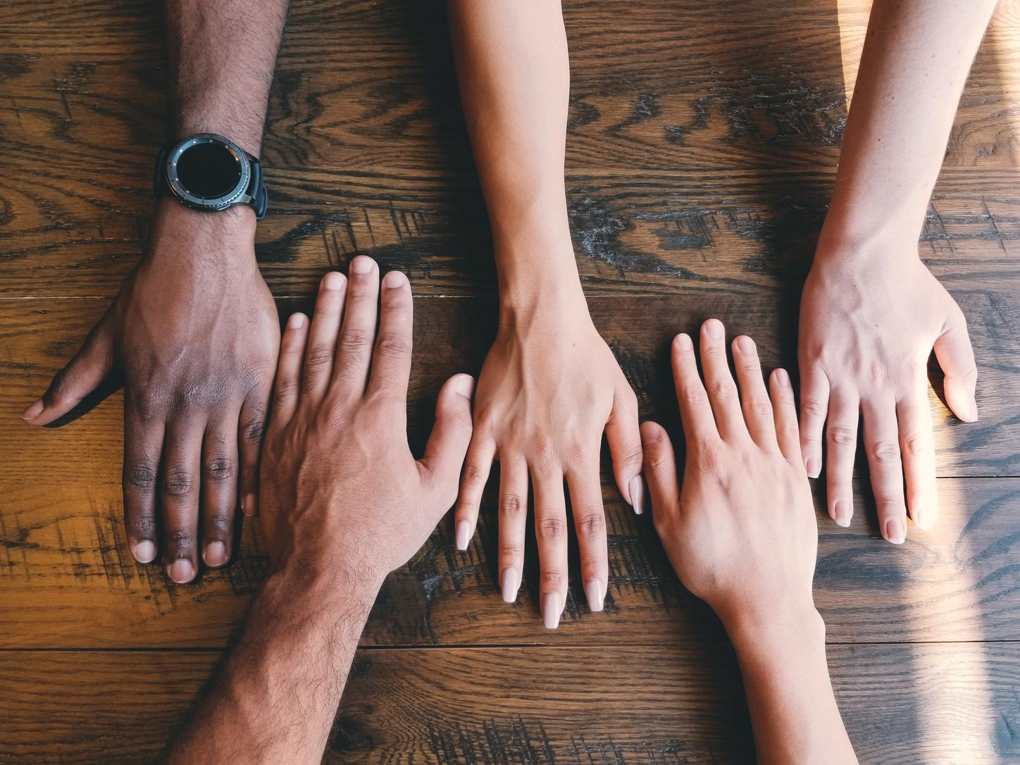 The image shows hands of different skin colors.