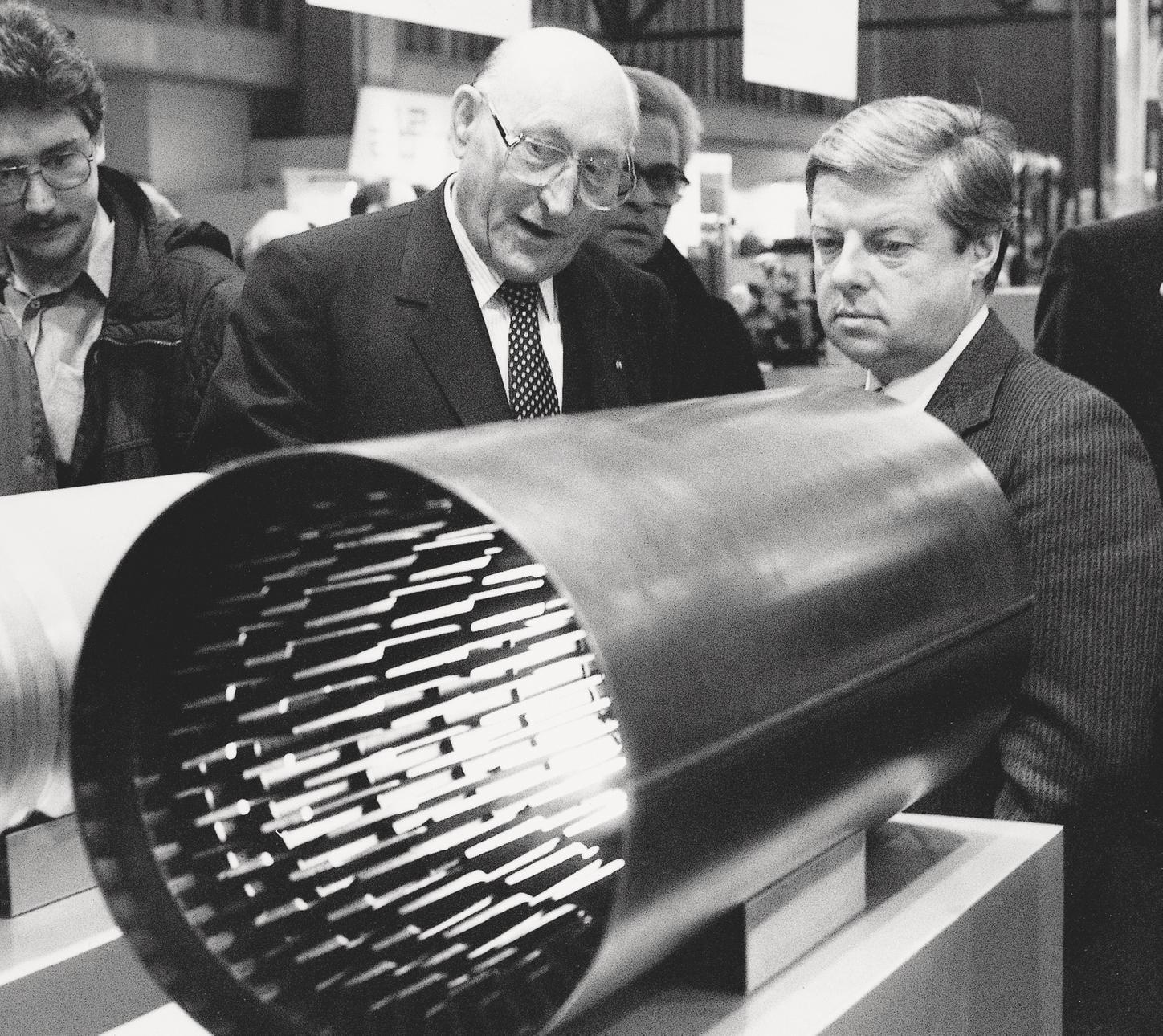 The picture shows Hans Viessmann and another person behind a biferral composite heating surface.