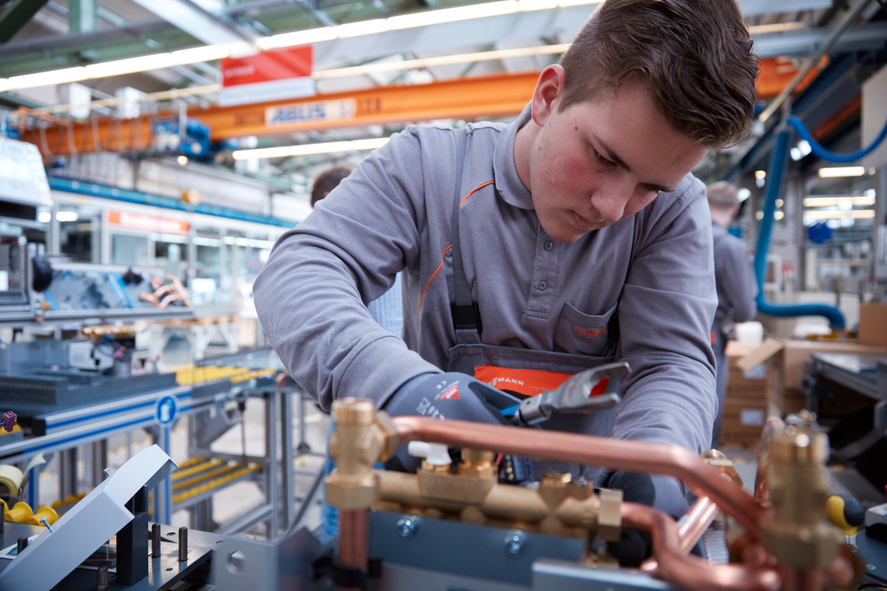 The image shows a trainee at the Viessmann factory.