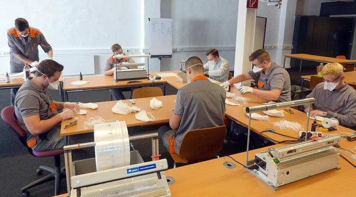 The picture shows seven trainees sewing disposable masks.