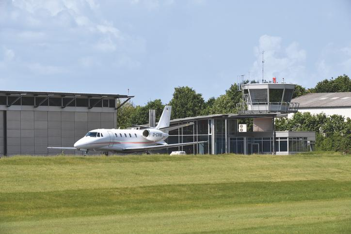 The image shows an aircraft in front of the hangar, lawn in the foreground.