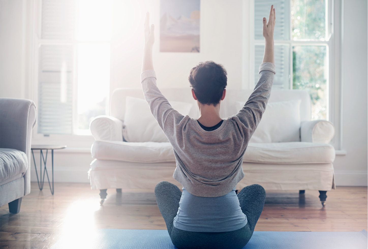 The picture shows a woman at home doing Yoga