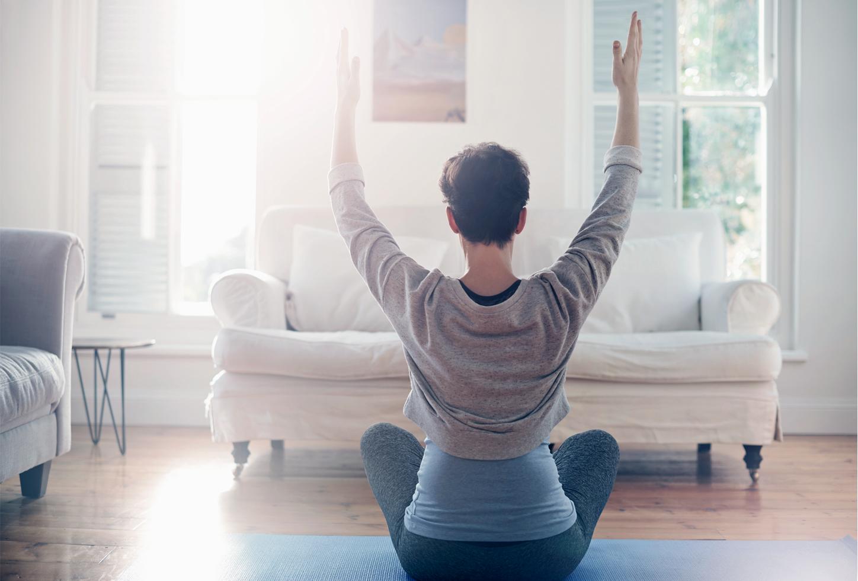 Das Bild zeigt eine Frau zuhause beim Yoga