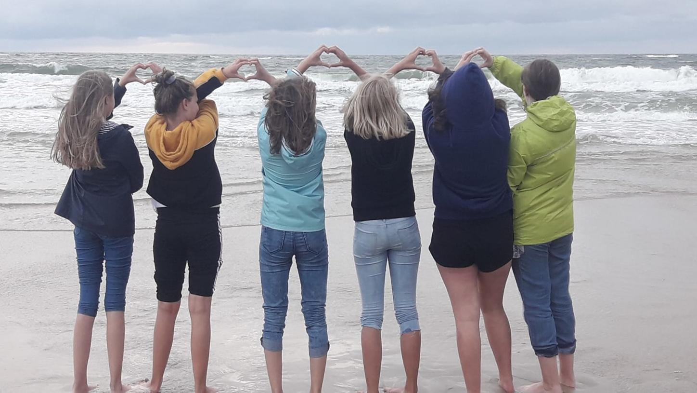 Das Bild zeigt eine Gruppe von hinten am Strand stehend.