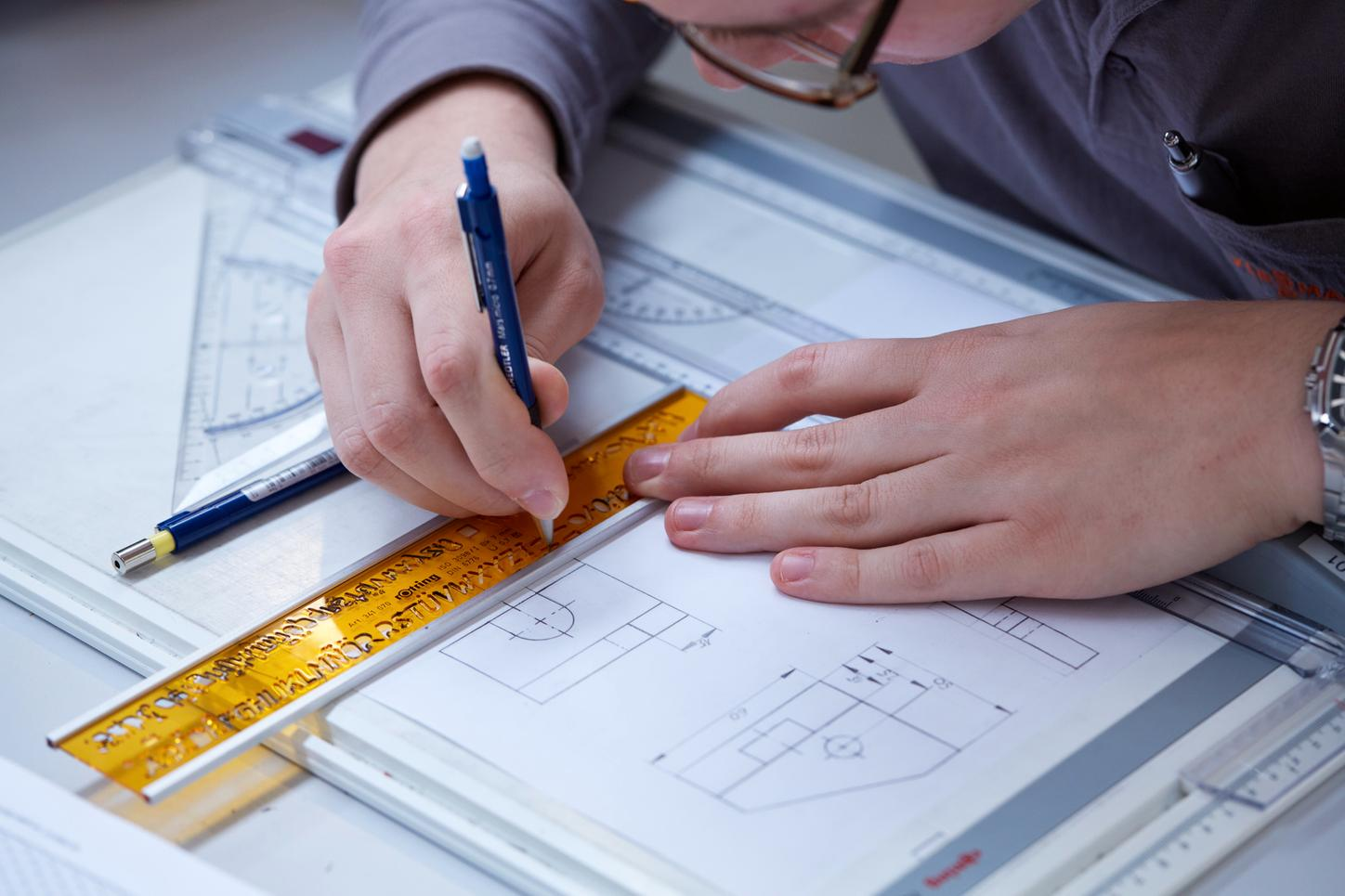 The image shows an employee creating a technical drawing.
