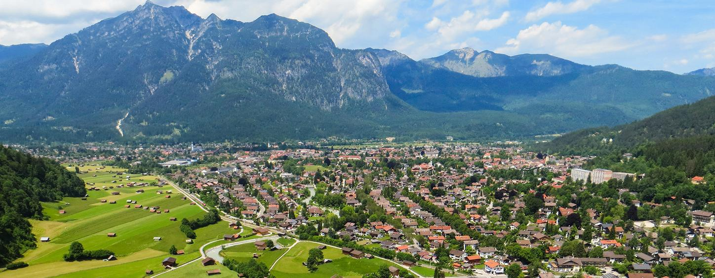 The picture shows a small town in a valley surrounded by nature and mountains as a symbol of sustainability.