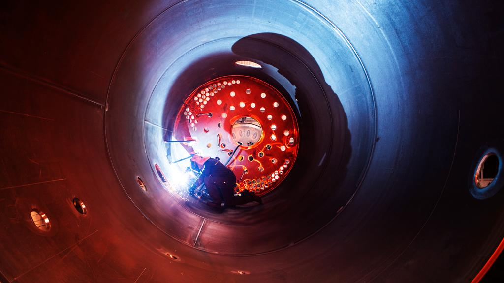 The picture shows welding work in a large industrial boiler.