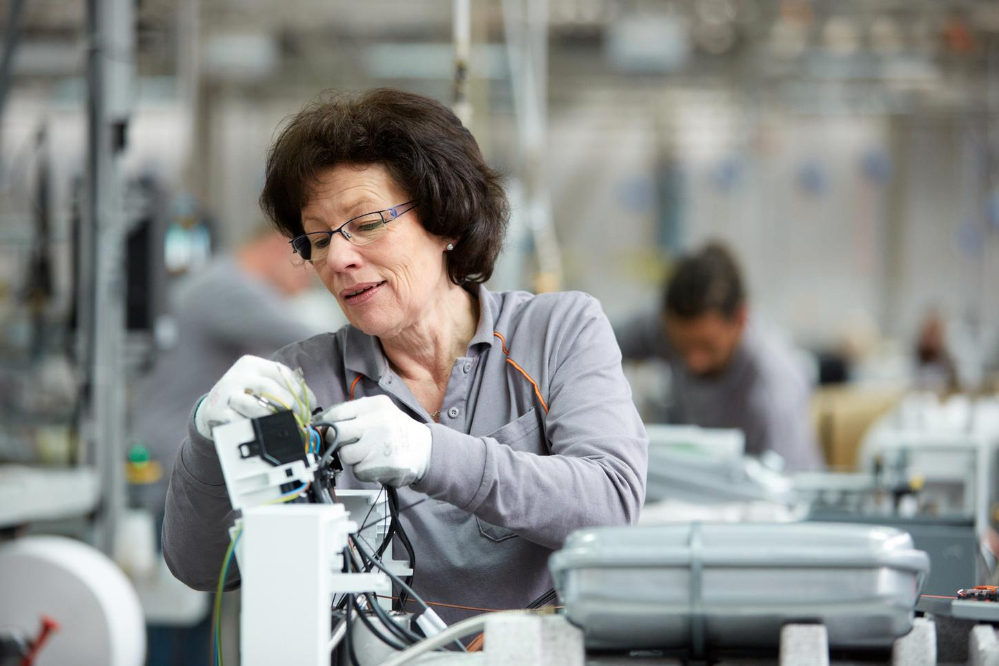 The image shows a female employee at the Allendorf factory.
