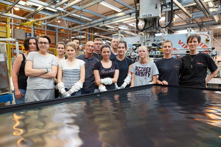 The image shows a group picture of Viessmann employees in a factory.
