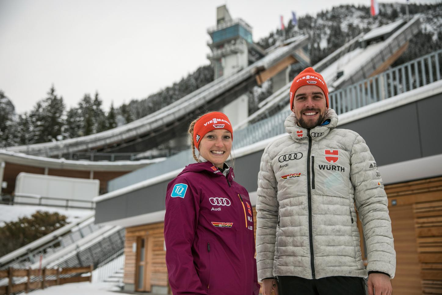 The picture shows the ski jumper Katharina Althaus and the Nordic combined athlete Johannes Rydzek in front of the ski jumping facility in their home town Oberstdorf