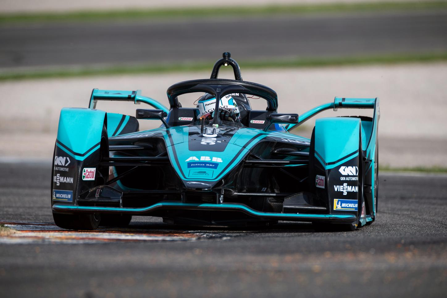 The picture shows a turquoise Formula E racing car.
